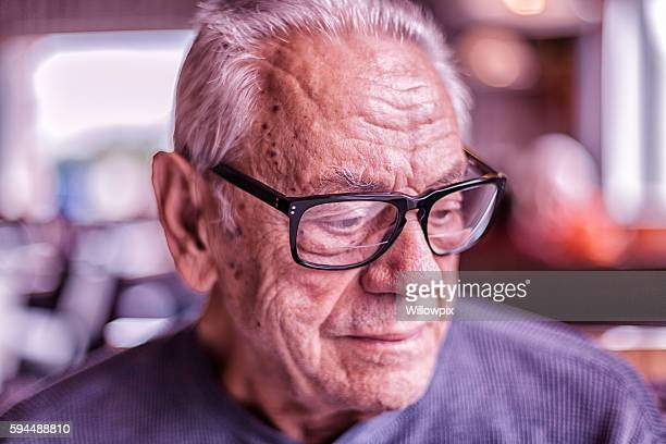 elderly dementia man waiting for breakfast looking down - warzen stock-fotos und bilder