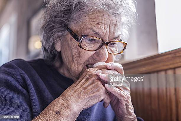 elderly dementia woman using teeth to open coffee cream container - bad teeth stock photos and pictures