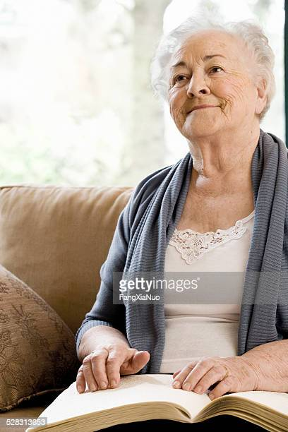 elderly disabled woman reading book with her hands - braille stock pictures, royalty-free photos & images