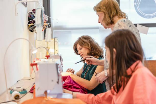 Elderly entrepreneur explaining seamstress about designing at fashion studio