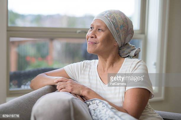 Elderly ethnic female cancer patient looking out a window