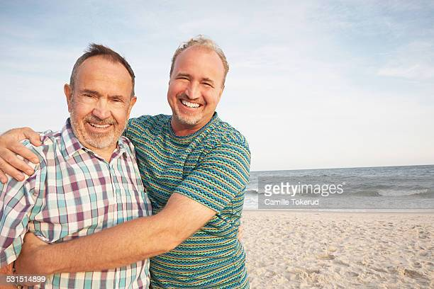 Elderly father and son at the beach smiling