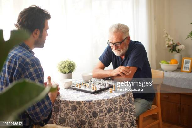 elderly father concentrate to playing chess game with son - brain  stock pictures, royalty-free photos & images