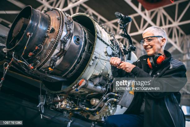 elderly female airplane engineer using a screwdriver to unscrew a part of a small jet engine on a private plane during maintenance in an aircraft hangar - airplane part stock photos and pictures