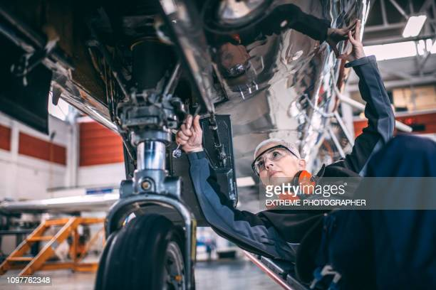Elderly female engineer using a socket wrench while repairing or doing maintenance to the landing gear of a small airplane in a maintenance hangar