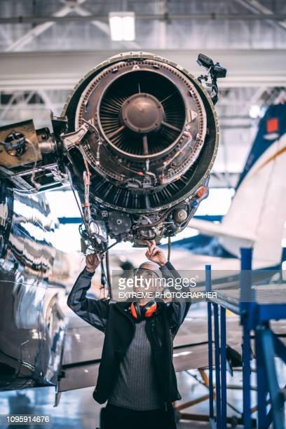 äldre kvinnlig ingenjör som arbetar på en flygplan jet motor i en hangar - luftfarkost bildbanksfoton och bilder