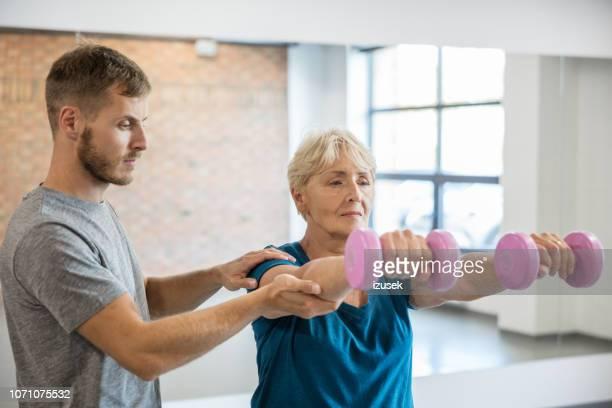 elderly female having rehabilitation at gym with trainer - izusek stock pictures, royalty-free photos & images