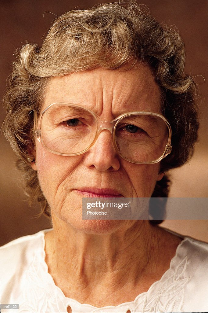 elderly female woman with glasses and short gray hair wearing a white shirt frowns at the camera and appears tired frustrated and concerned : Stockfoto
