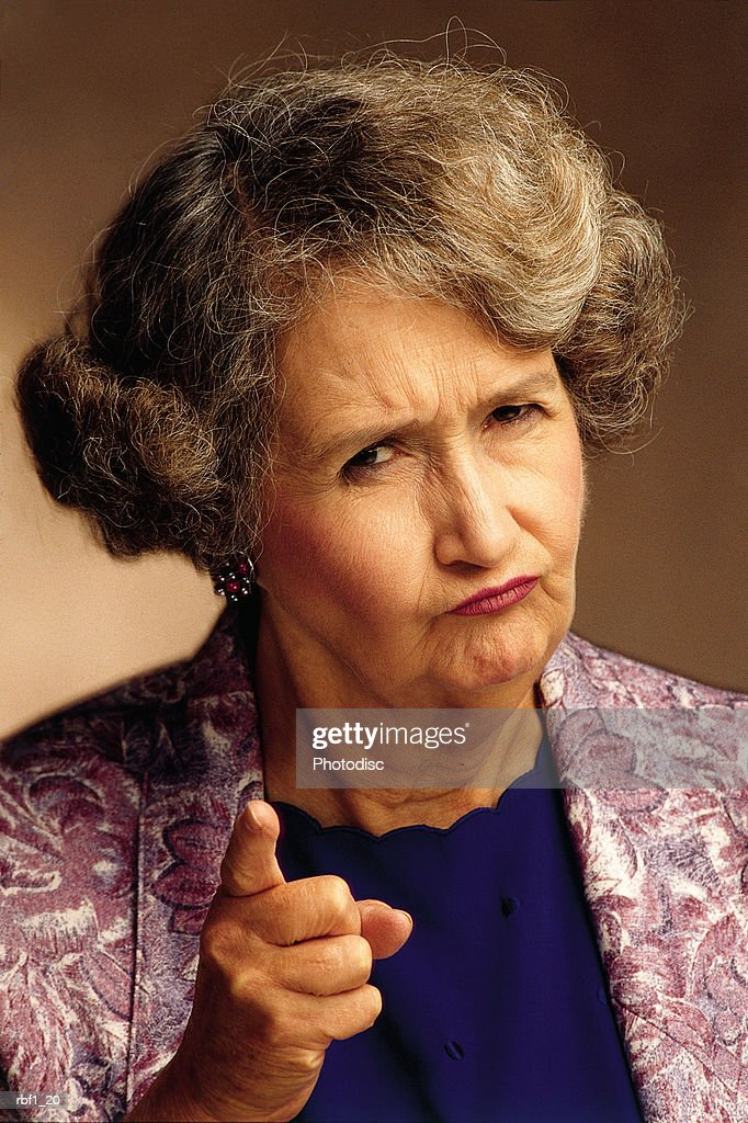elderly female woman with shorter graying hair wearing a purple jacket and blue shirt frowns and gives the camera or imaginary person a disapproving look while she shakes her finger and appears to be scolding someone : Stockfoto
