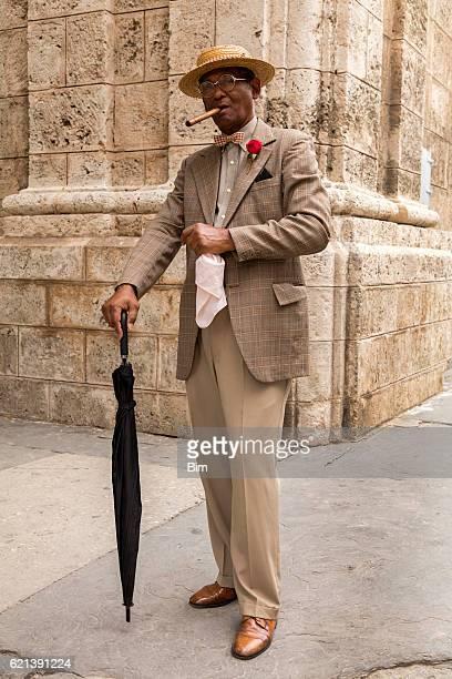 Elderly gentleman with cigar and umbrella in Havana, Cuba