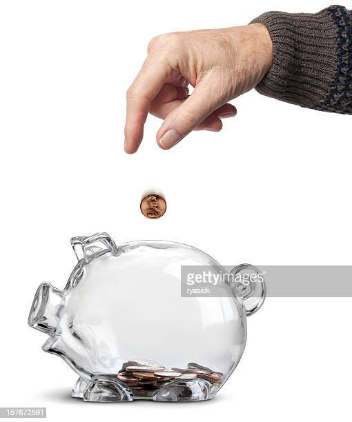 elderly hand dropping coins into almost empty piggy bank isolated - small group of objects stock pictures, royalty-free photos & images
