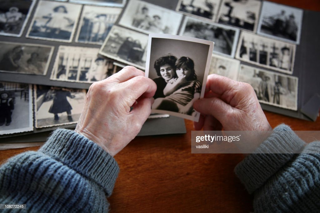 Elderly hands looking at old photos of self and family : Stock Photo