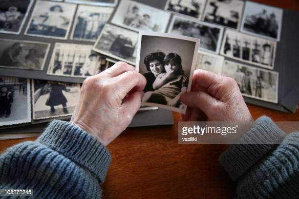 elderly hands looking at old photos of self and family - photography stockfoto's en -beelden