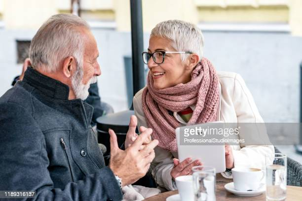 elderly handsome couple enjoying in city cafe during a cold winter day - studio city stock pictures, royalty-free photos & images