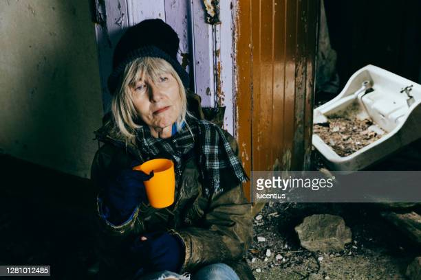 elderly homeless senior woman in an abandoned ruin - homelessness stock pictures, royalty-free photos & images
