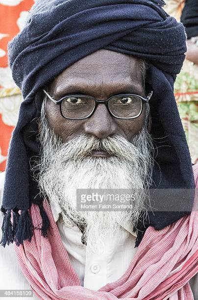 Elderly Indian man with a big white beard wearing a common scarf as a turban