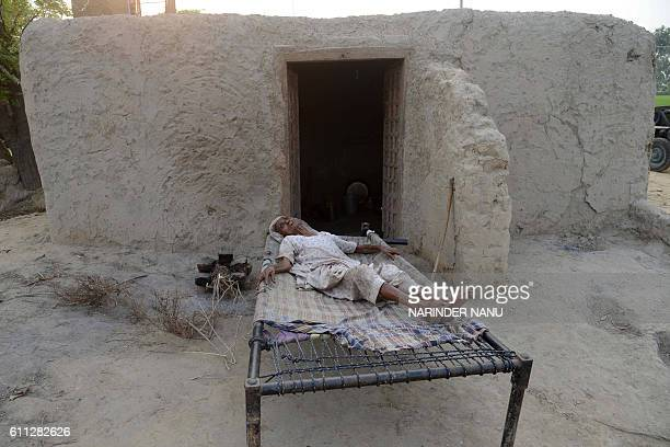 TOPSHOT Elderly Indian villager Teji Kaur takes a rest on a bed at the border village Dauke about 40 kms from Amritsar on September 29 after the...