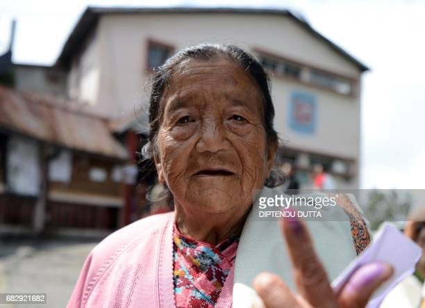 Elderly Indian voter Pasang Lamu Sherpa shows her inked finger after casting her vote at a polling station in Kurseong on May 14 for local municipal...