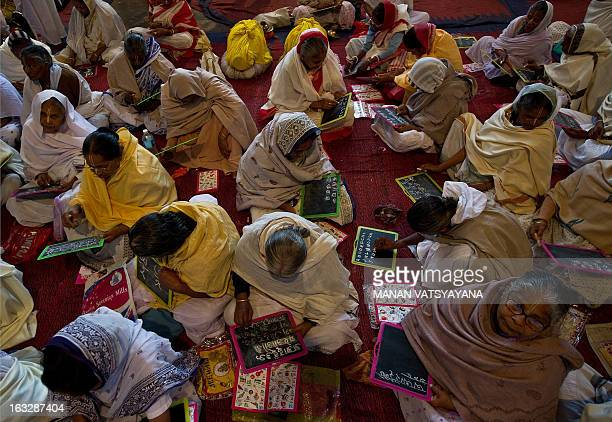 Elderly Indian widows attend a reading and writing class at the Mahila Ashram a shelter home for widows in Vrindavan some 150 kms southeast of New...