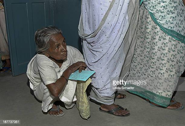 Elderly Indian woman waits in a long line outside the Assembly of God free medical clinic to see a doctor and to receive medicine. She has her...