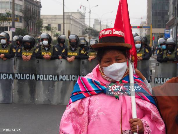 Elderly indigenous woman carrying a flag when on the day of Pedro Castillo's presidential inauguration his supporters take to the streets to demand a...