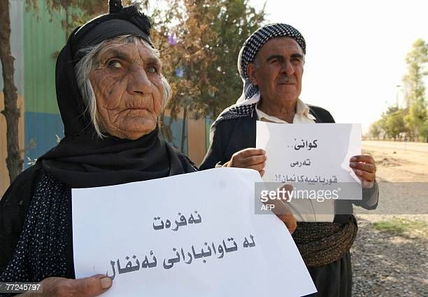 Elderly Iraqi Kurds hold a sign in Kurdish demanding the acceleration of the execution of Chemical Ali and asking for financial compensation for...