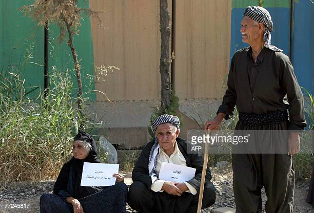 Elderly Iraqi Kurds hold signs in Kurdish demanding the acceleration of the execution of Chemical Ali and asking for financial compensation for Anfal...