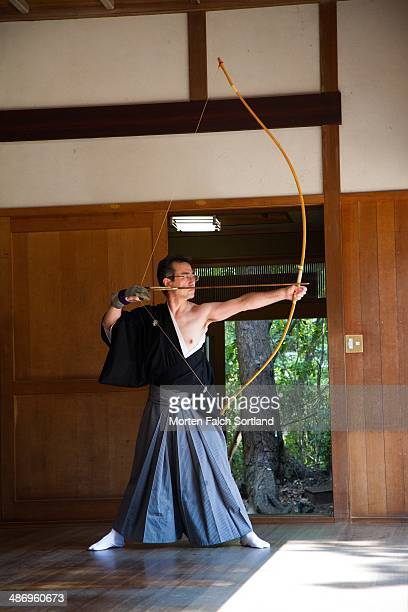 Elderly Japanese man aiming his Kyudo bow for shooting