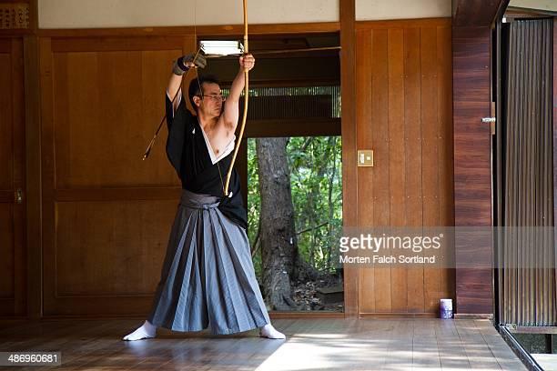 Elderly Japanese man preparing his Kyudo bow for shooting