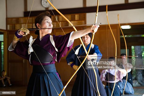 Elderly Japanese woman aiming her Kyudo bow and arrow for shooting