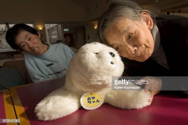 elderly japanese woman with paro, a robotic seal - paro stock-fotos und bilder