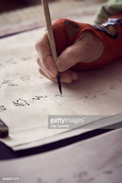 elderly japanese Woman writing calligraphy, close up of hand