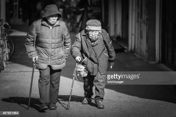 elderly japanese women walking down street using sticks tokyo japan - black alley stock photos and pictures