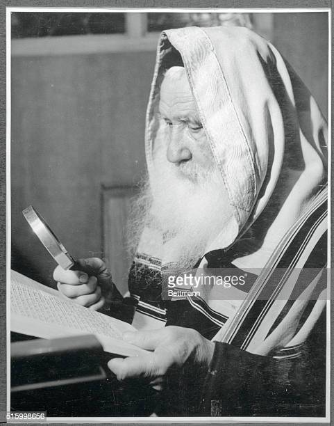 Elderly Jewish man wearing a prayer shawl reads a book in Hebrew using a magnifying glass