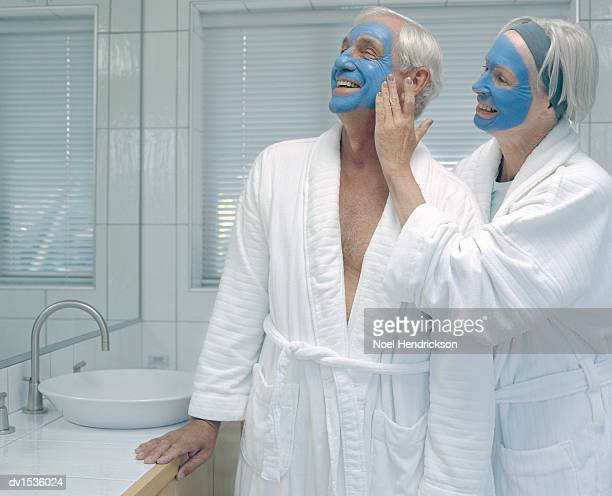 Elderly Lady Assists and Elderly Man to Apply a Face-Pack