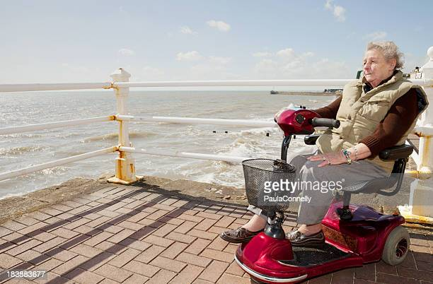 elderly lady by the sea - mobility scooter stock photos and pictures