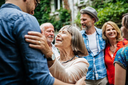 Elderly Lady Greeting Family Members In Courtyard - gettyimageskorea