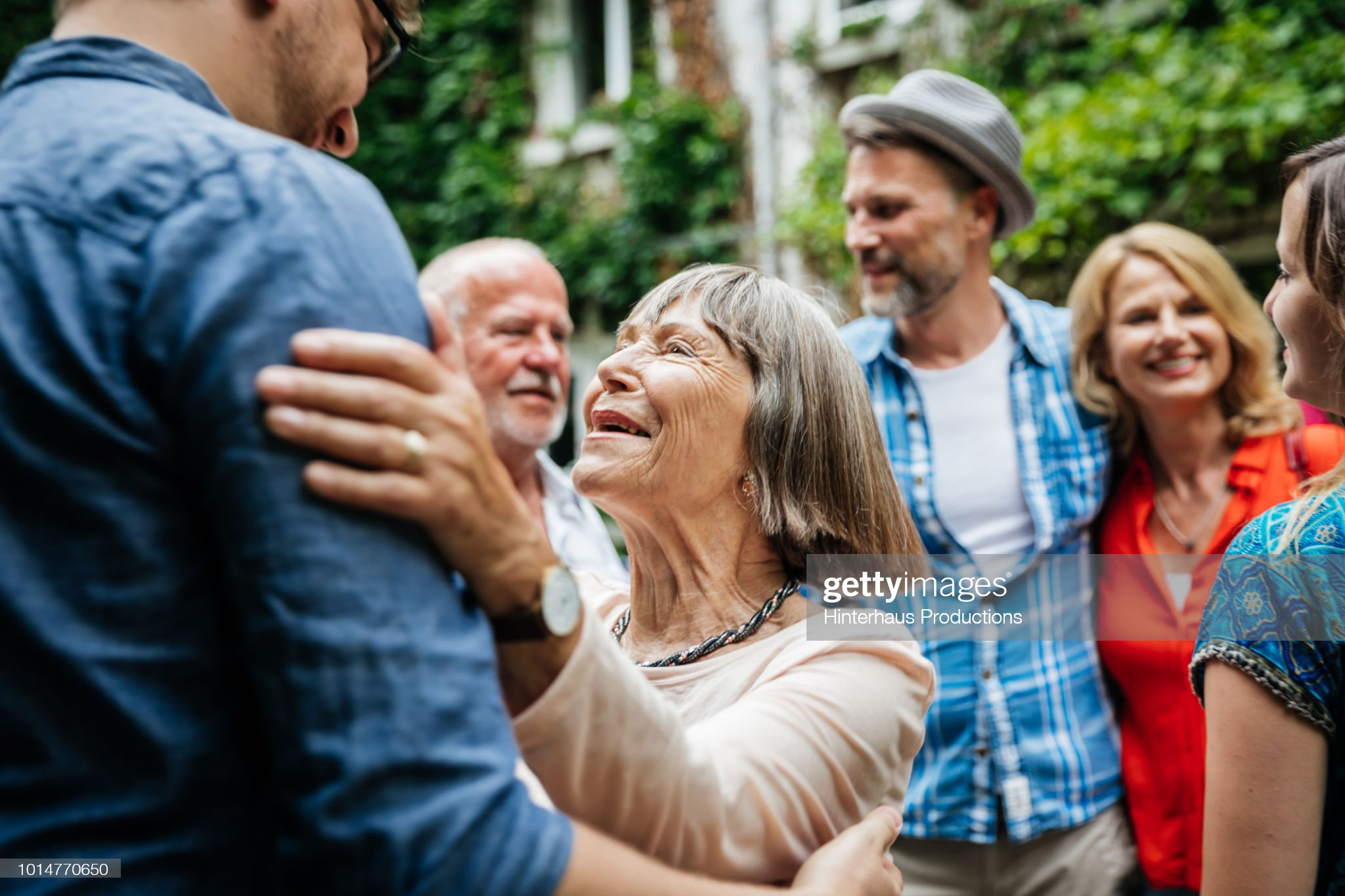 Elderly Lady Greeting Family Members In Courtyard : Stock Photo