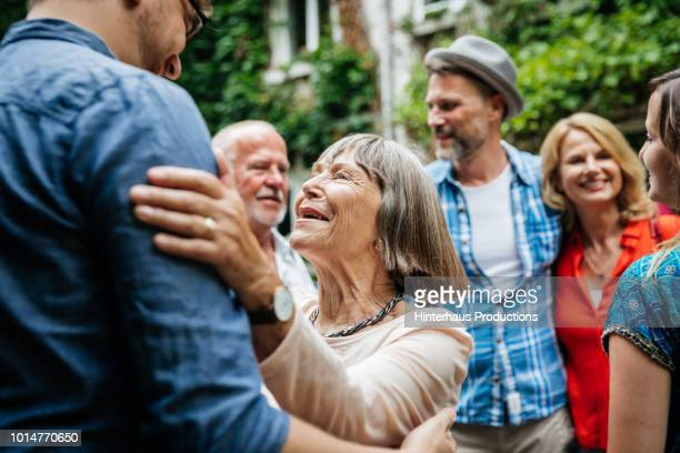 elderly lady greeting family members in courtyard - zusammenhalt stock-fotos und bilder