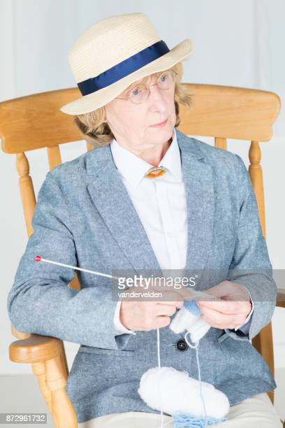 Elderly lady in 1930s clothes in her rocking chair knitting