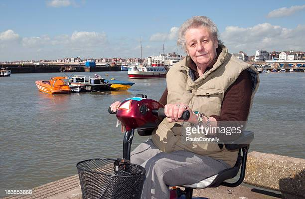 elderly lady on mobility scooter - mobility scooter stock photos and pictures