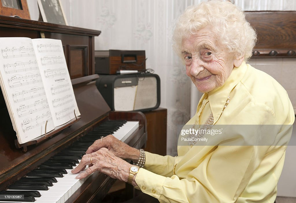 Elderly lady playing piano at home : Stock Photo