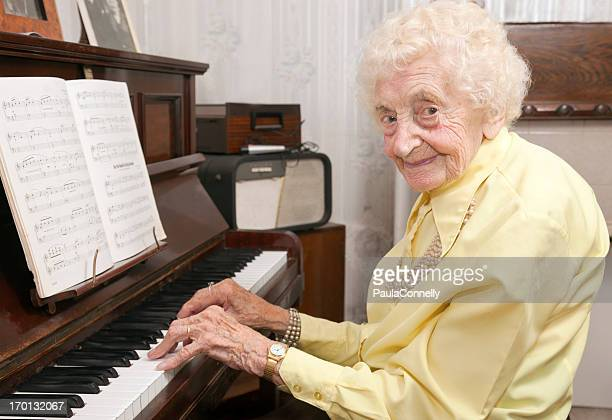 Elderly lady playing piano at home