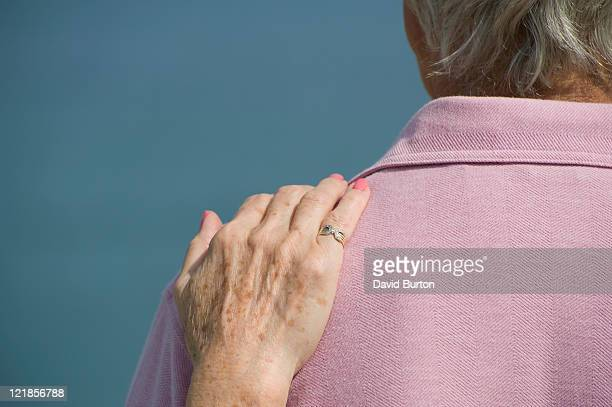 Elderly lady resting her hand on her partners shoulder