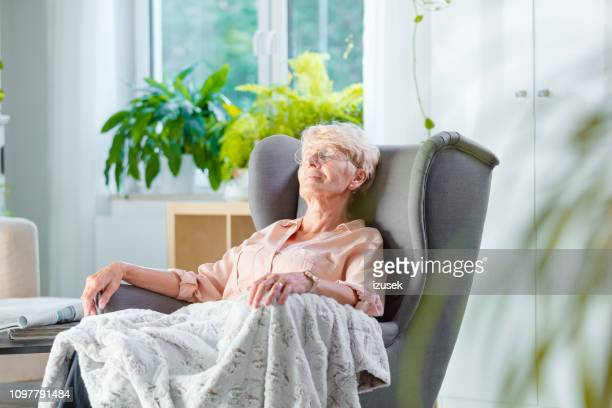 elderly lady resting in an armchair in her room - resting stock pictures, royalty-free photos & images