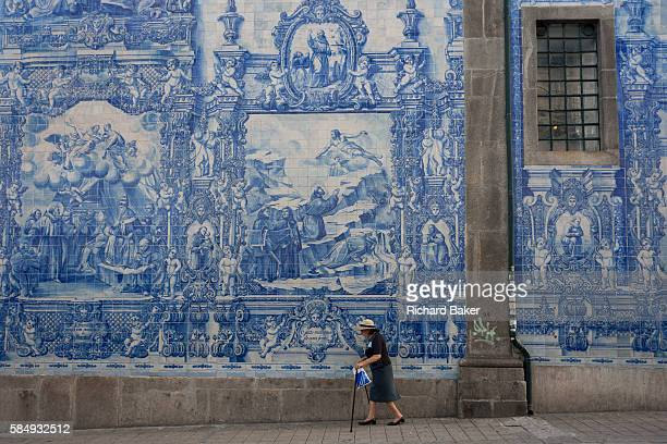 Elderly lady walks with sticks along the Rua de Fernandes Tomas with Azulejo tiles on the exterior of Capela Das Almas on 20th July in Porto Portugal...