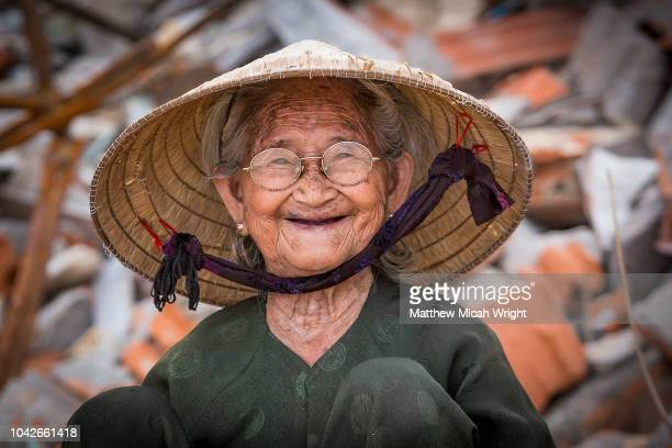 a elderly local woman smiles as she takes a break from work in bai xep; a quiet remote fishing village off the tourist path, 10km from the major city of qui nhon. - vietnamien photos et images de collection