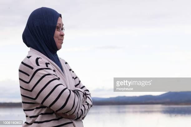 湖 wivenhoe に立って高齢者マレー女性 - スカルキャップ ストックフォトと画像
