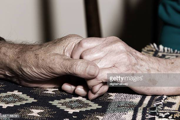 Elderly male and female hand hold over a dark table cloth