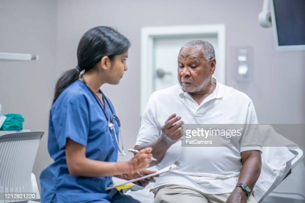 elderly male patient talking with female doctor stock photo - medical research stock pictures, royalty-free photos & images